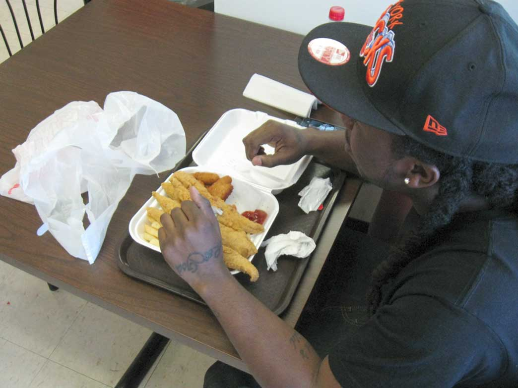 24-year old Issac Pettiford enjoys his tray of whiting, hushpuppies, and fries while waiting his turn for a haircut next door. (Photo: Marissa Peterson)