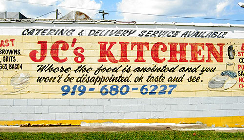 The side of JC's Kitchen is painted with a mural touting the food and the motto of the restaurant. (Staff photo by Robert K. Bryan)
