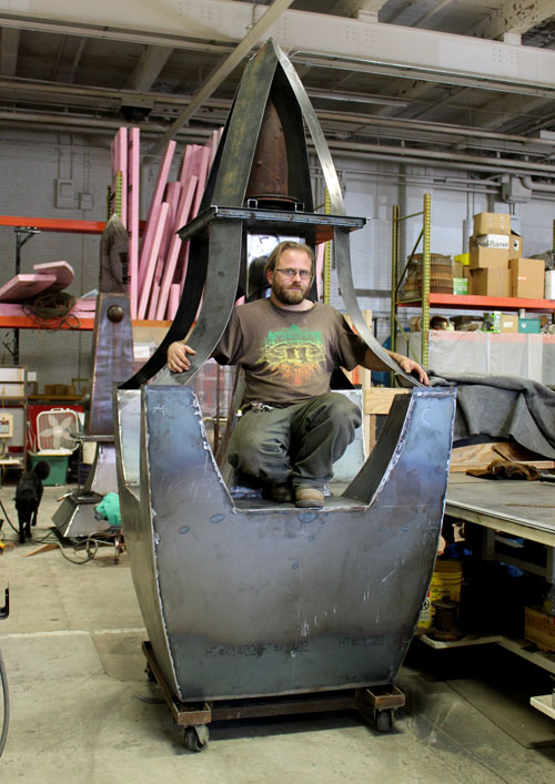 Sculptor Tripp Jarvis poses for a picture crouching down into one of his sculptures. (Staff photo by Naomi Marín-Rosario)