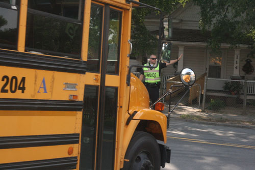 A Durham Police Officer helps buses leave the school safely on a recent day at Maureen Joy Charter School. Photo by Sheila Rosier.