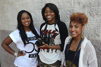 Hillside Chronicle photographers, left to right, Breana Kea, Kristen Mayo and Taylor Owens, show off the new Nikon, donated by the Durham VOICE on behalf of Randall and Elizabeth Williams of Raleigh in honor of their late son, Steele. (Staff photo by Evey Wilson)