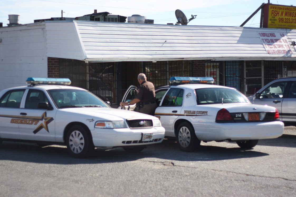 A Durham County Sheriff gets into his police cruiser after leaving Fish-N-Wings on Fayetteville St, located in front of one of the proposed headquarters locations. (Staff photo by Robert Lewis)