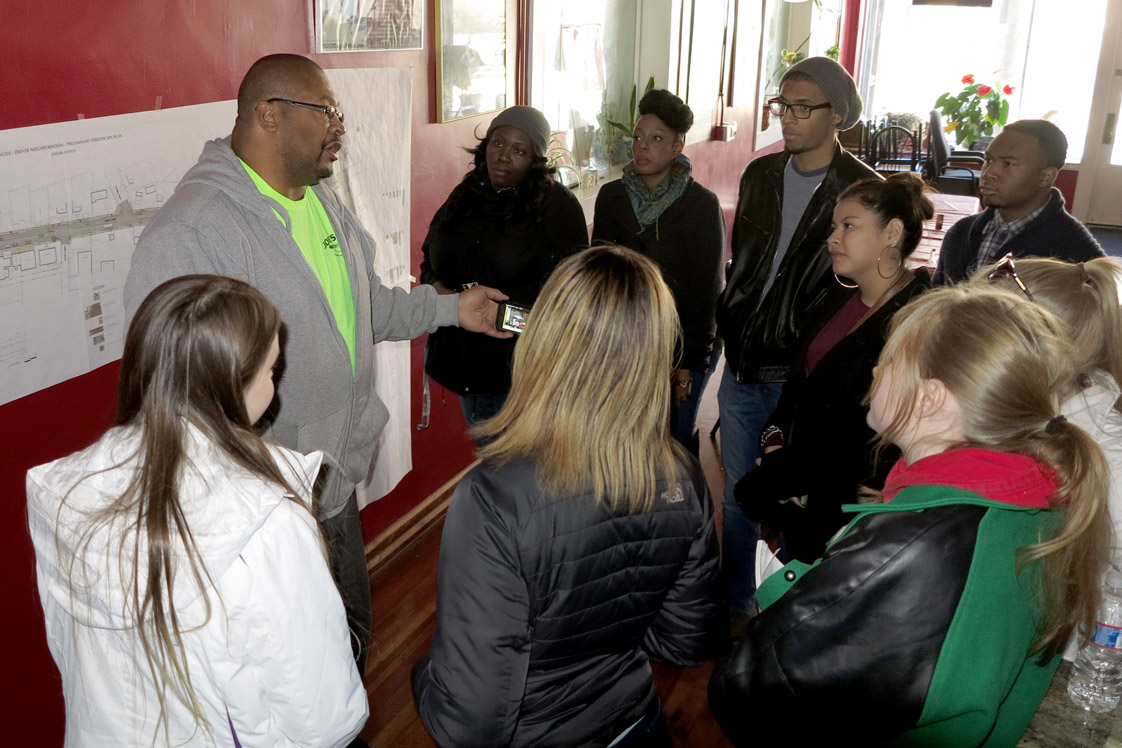 Hosting a group of visiting students from NC Central and UNC, Joe Bushfan explains that his neighborhood is on the come-back. (Staff photo by Jock Lauterer)