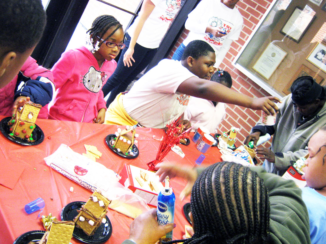 The event included recreational holiday activities for the family like face painting and making gingerbread houses. Here kids make tasty gingerbread houses with parents.