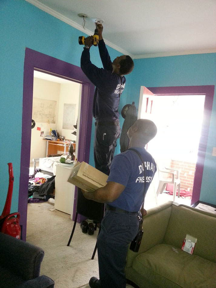 Durham Firefighters (left to right) Kendrick Campbell and Edwin McDonald install smoke alarm in Dupree residents home. (Staff photo by Myava Mitchell)