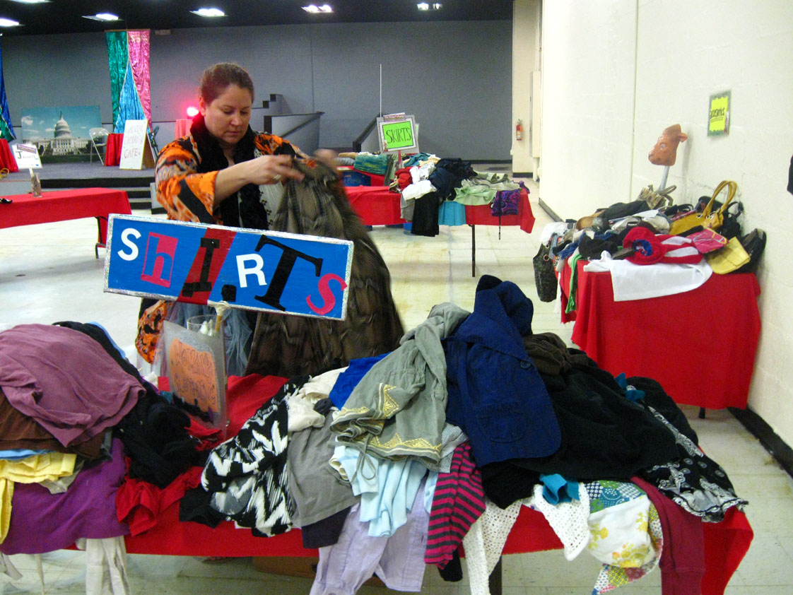 Heather Cashwell, a first-time swap volunteer, sets up for the day by putting out piles of donated clothes the Scrap Exchange gathered for the event.