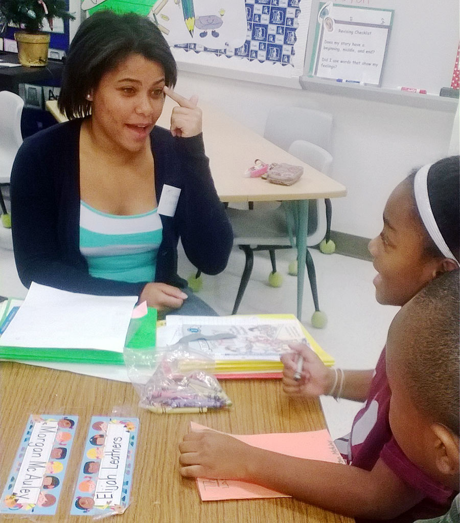 "Junior Bianca Decatur explains the Spanish term for ""eye"" to second grader Morgan McAuley. Courtesy of The Round Table"