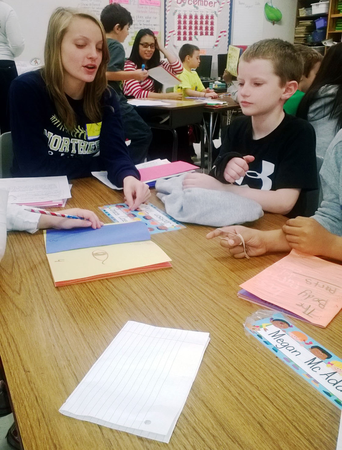 Junior Molly Monsees helps Little River second grader Jackson Tilley learn Spanish body parts.