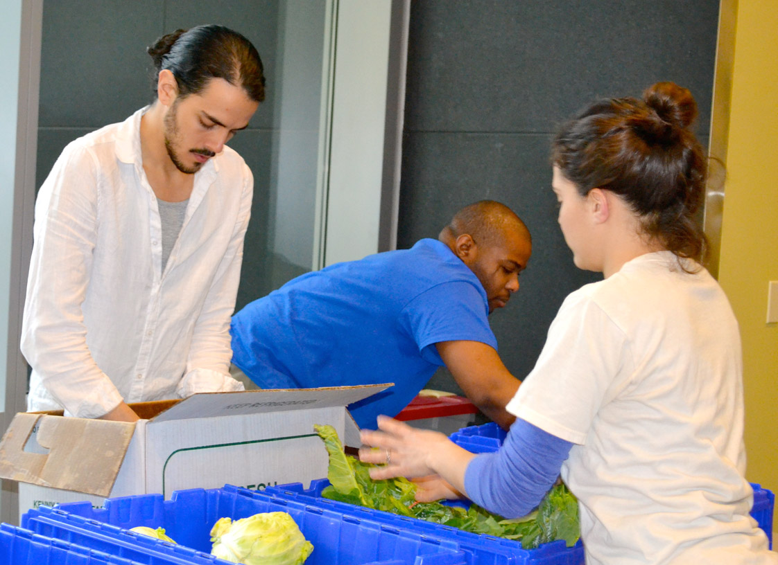 Spencer Wright, Bernard Lile and Karla Capacetti organizing the produce (Staff photo by Alyssa Armstrong)