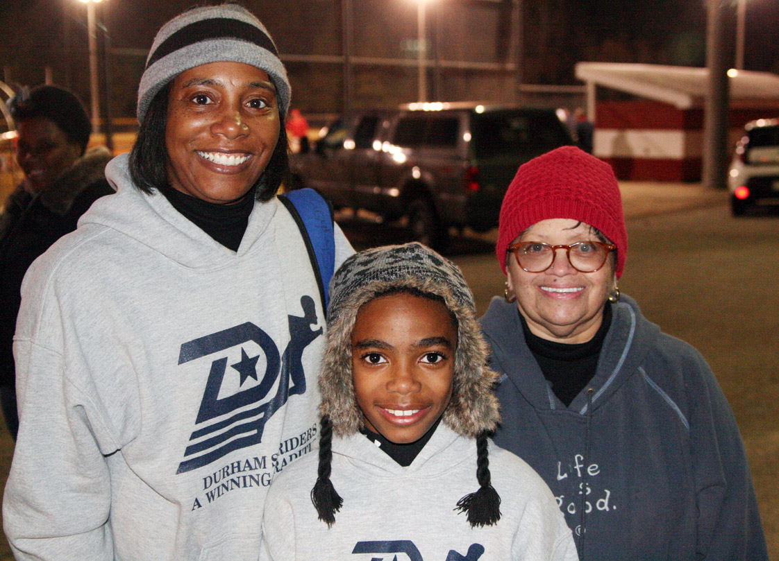 """cold drizzly evening did not slow down the first day of outdoor spring practice for the Durham Striders Youth Association. Coaches Sonya Stephens (left) and Brenda """"Coach Doc"""" Armstrong (right) congratulate national indoor long jump champ Caleb Stephens of Rolesville on a good workout. Coached by age group and skill level, the Striders practice several times a week and compete in developmental meets two to three times a month during April and May. Photo by Koonce"""