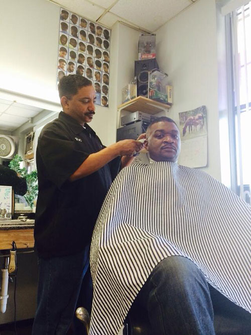 Imperial Barber shop manager Victor Hughes, cutting some hair and enforcing a good and healthy environment for the community.