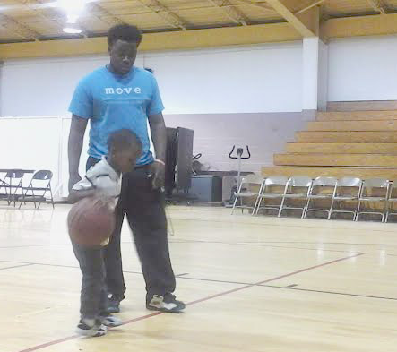 Lawrence Mitchell, W.D. Hill facility attendant, and Damien Wynn, a summer attendee, school each other on the fundamentals of basketball in W.D. Hill Recreation Center gymnasium. (Staff photo by Terumi Dowdy)