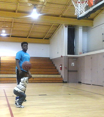 Damien Wynn, a W.D. Hill Recreation summer program attendee, practices his free throw as Lawrence Mitchell, W.D. Hill facility attendant, looks on. -       (Staff photo by Terumi Dowdy)