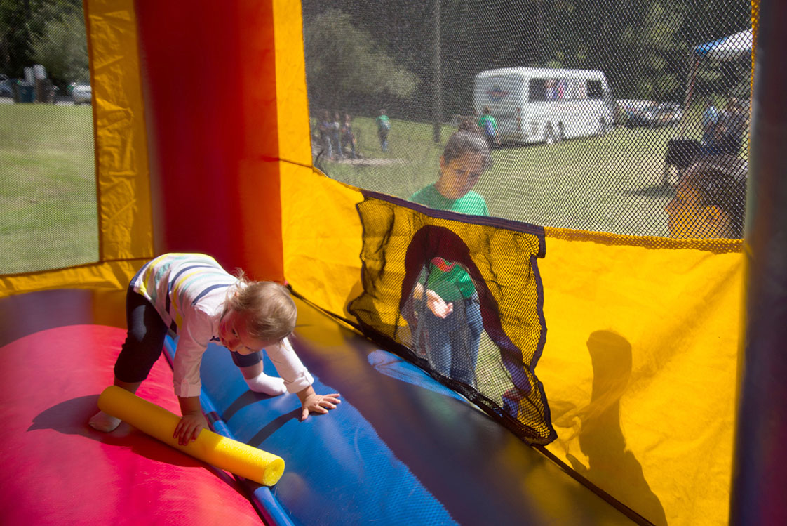 "Volunteering is a family affair for Dariana, 18, and Yessica, 17, Vargas, who watch as Anita, 2, enjoys her first festival experience in the ""bounce house"" at Durham's Latino Fest on September 27. Dariana said, ""I like giving back to the community, [volunteering] is like giving a little happiness."" (staff photo by Robert Berges)"
