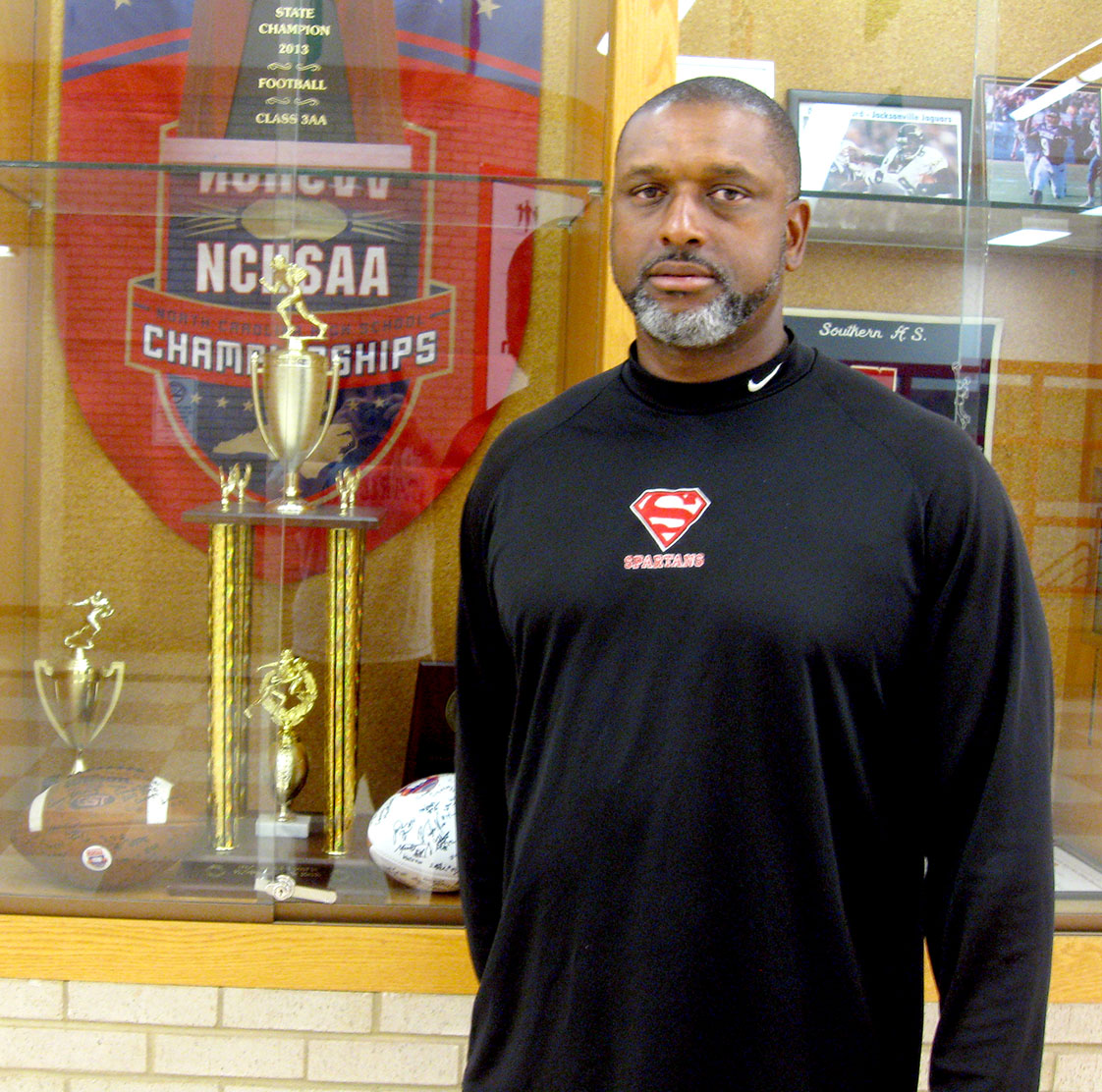 Darius Robinson stands next to Southern High School's 2013 NCHSAA Class 3-AA state championship trophy, the first in school history. Robinson was an assistant coach on last year's squad, but took over as head coach at season's end. The Spartans are currently off to a 3-0 start this year. (Staff photo by Andrew Forrest)