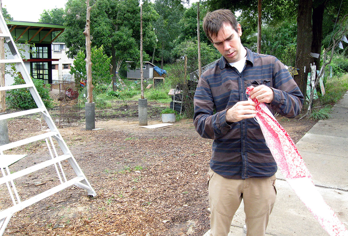SEEDS volunteer Stephen Druesedow works on putting flags together to hang up around the SEEDS campus. For Druesedow, volunteering at SEEDS allows for him to learn about community gardening, while also making new friendships. (Staff photo by Andrew Forrest)