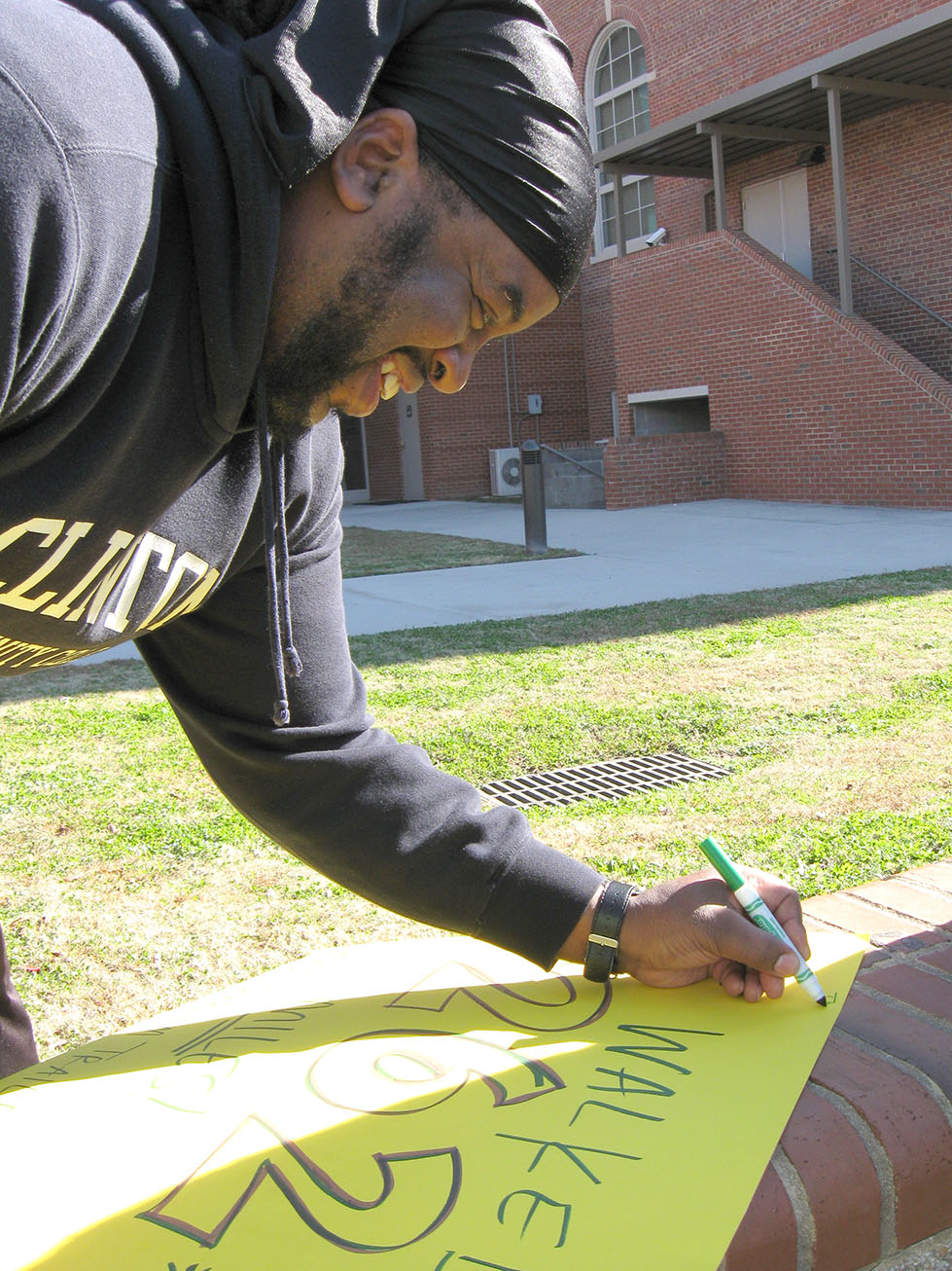 "Darryl Barnes signs the East Durham Trail Blazers' poster, writing his name and miles tallied. Darryl walked 18 miles in six weeks, and his wife, Lanishia, walked 22. ""I've been feeling a lot better lately,"" he said."