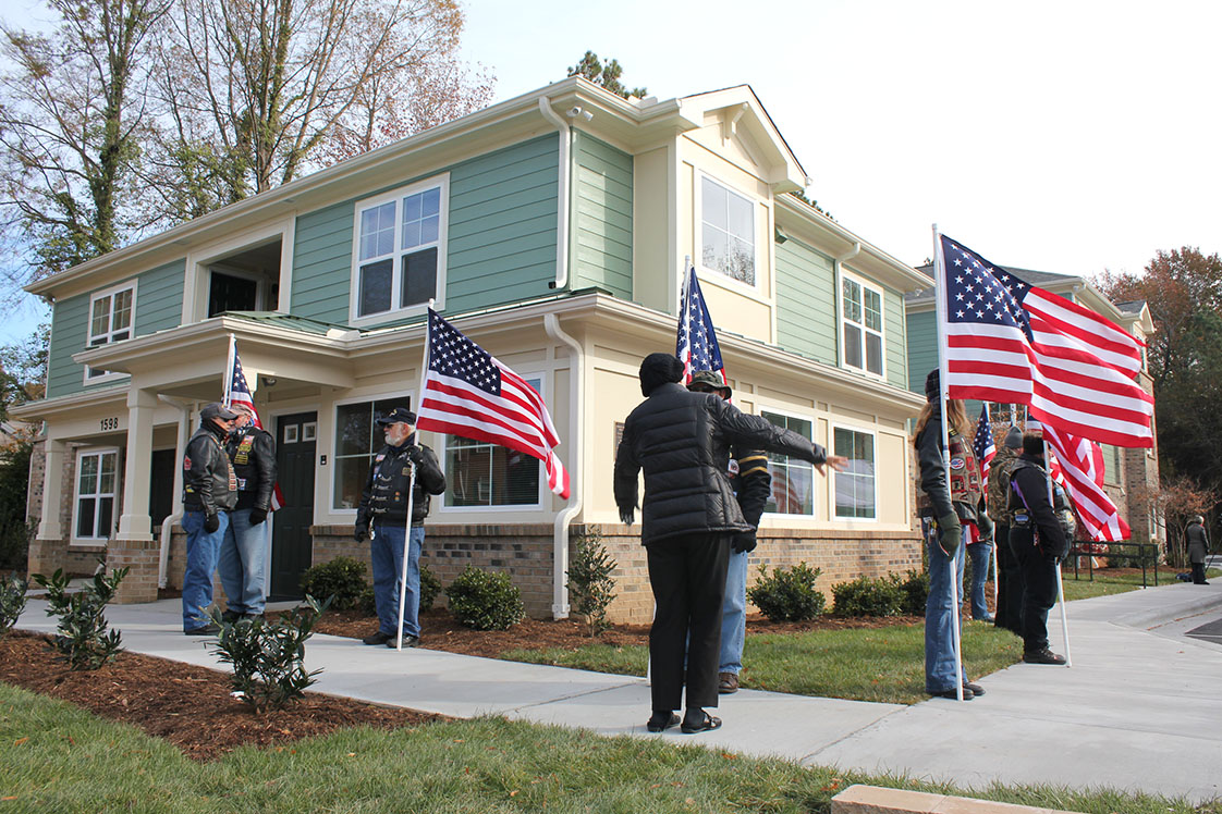 The Patriot Guard, a group of veterans who attend local events to honor military folks, gripped their flags on the frozen sidewalk outside of the new Denson Apartments for Veterans. (Staff photo by Mary Alta Feddeman)