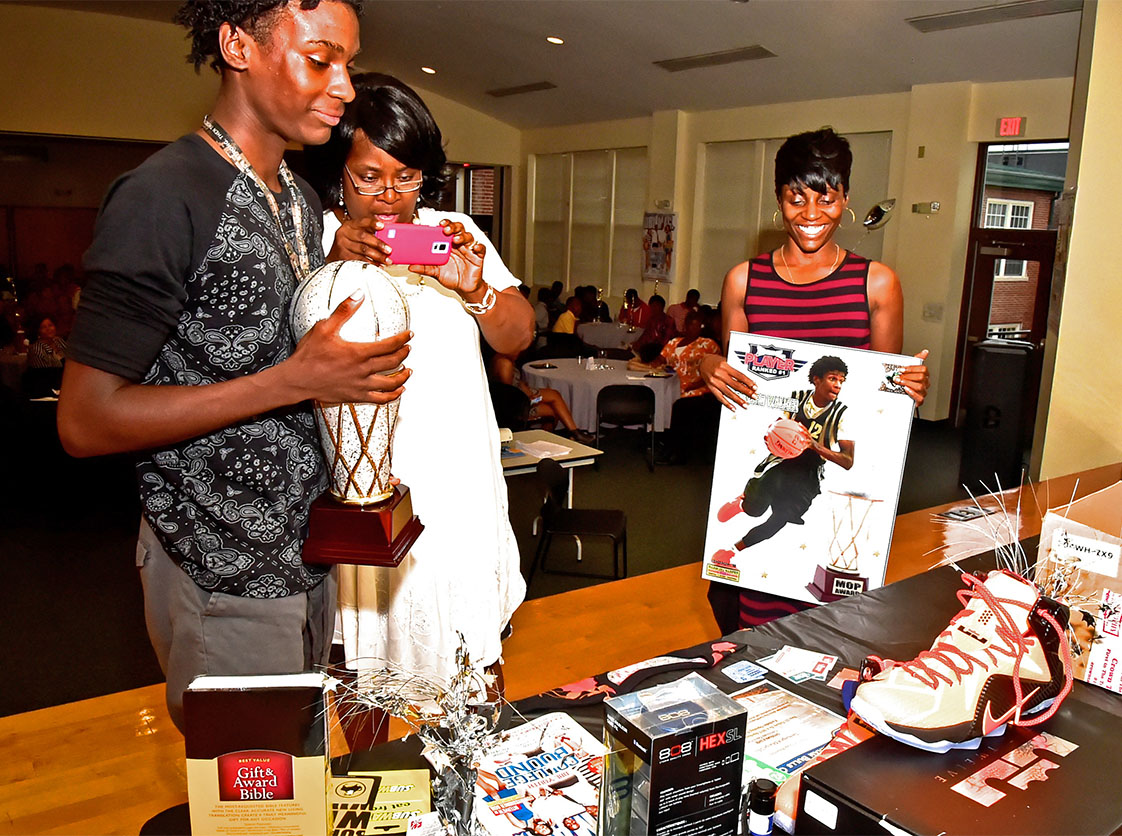 Edward Walker, DBL Most Outstanding Player Award recipient, admires prizes he received from the DBL for his achievement. Walker's mother, Mrs. Olympia, holds a poster of Walker as DBL team mom Gwendolyn Daye captures the event with a camera. (Photo courtesy of DBL)