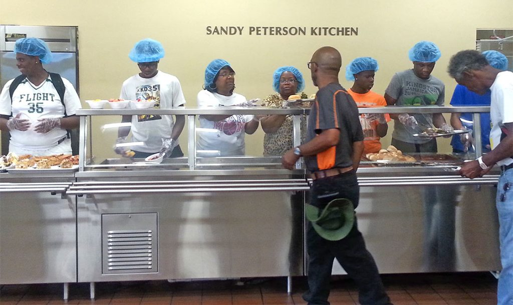 Players and team moms work the kitchen at the Durham Rescue Mission as part of the DBL's weekly community service. (Photo courtesy of DBL)