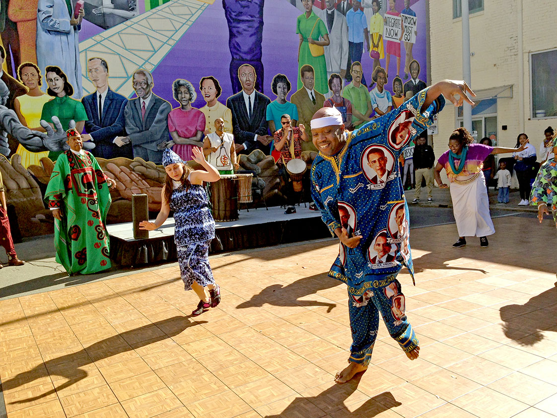 McDaniel Roberts leads the African-American Dance Ensemble in front of the newly finished mural. (Staff photo by Tyler Vahan)