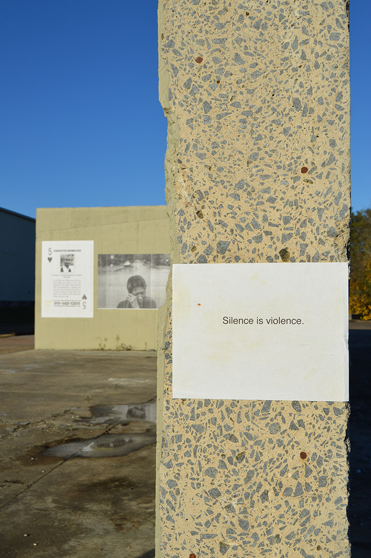 """Silence is violence,"" reads one of the markers at the Justin Cook photo exhibit. (Staff photo by Danny Nett)"