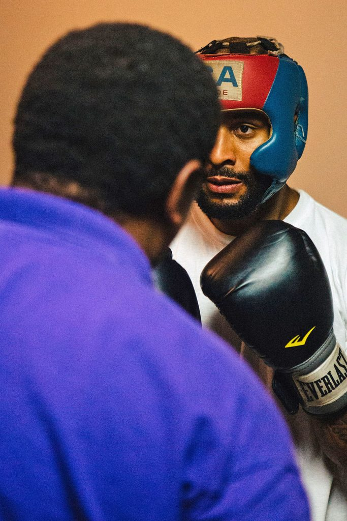 David Johnson, 28, concentrates on his form while preparing for combination punches with Bishop Arnold Harris. Bishop Harris helps David with words of encouragement. (Staff photo by Bruce dePyssler)