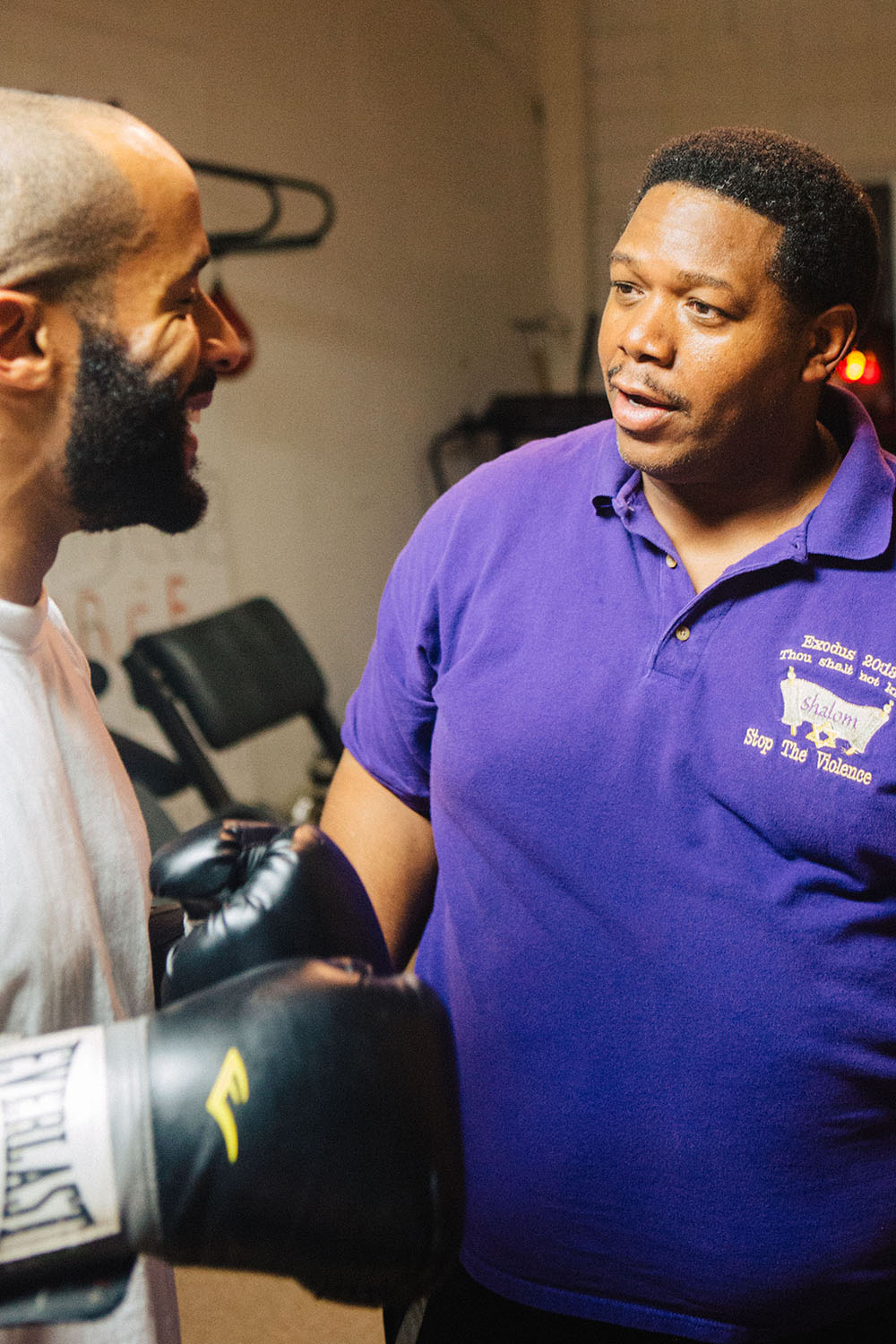 David Johnson, 28, takes a moment to laugh while Bishop Arnold Harris jokes with him. David enjoys his new hobby of boxing at The Gym of Hard Knocks. (Staff photo by Bruce dePyssler)