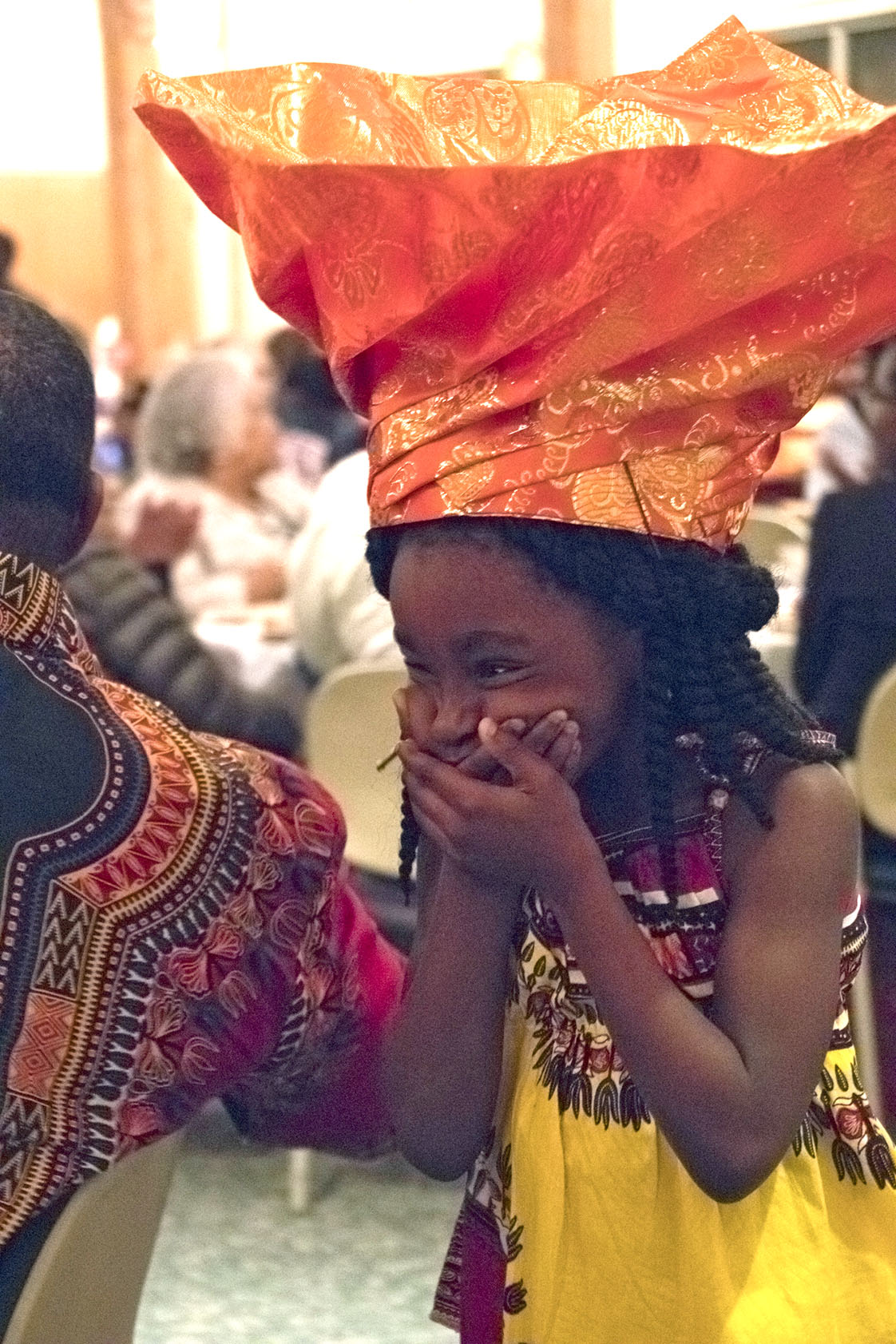 One of the many child models of the evening, Laurina Tamba, giggles as she makes her modeling debut during the Liberian dinner and fashion show at St. Philips on Saturday, Oct. 15. (Staff photo by Brenna Elmore)