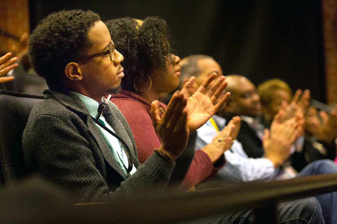 "Joshua Aurelius Galloway applauds a speaker during Black Wall Street Homecoming in the Full Frame Theater on Oct. 14, 2016. Galloway said that he missed Homecoming last year because he did not hear about it in time. This year, he got tickets and drove to Durham from Charlotte to attend. ""Moments of inspiration can happen here in 20 minutes as opposed to opening 400 tabs on Google Chrome,"" Galloway said. He has run a creative agency called Eyedentity Labs for five years and Neck of the Woods -- a busniess that makes wooden bow ties -- for two years. (Staff photo by Rob Gourley)"