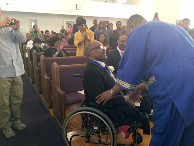 Pastor Michael Page pins honoree Ervin Hester, the first African-American news anchor in Durham, during the 2016 African-American History Month celebration. (Photo courtesy of Pastor Michael Page)