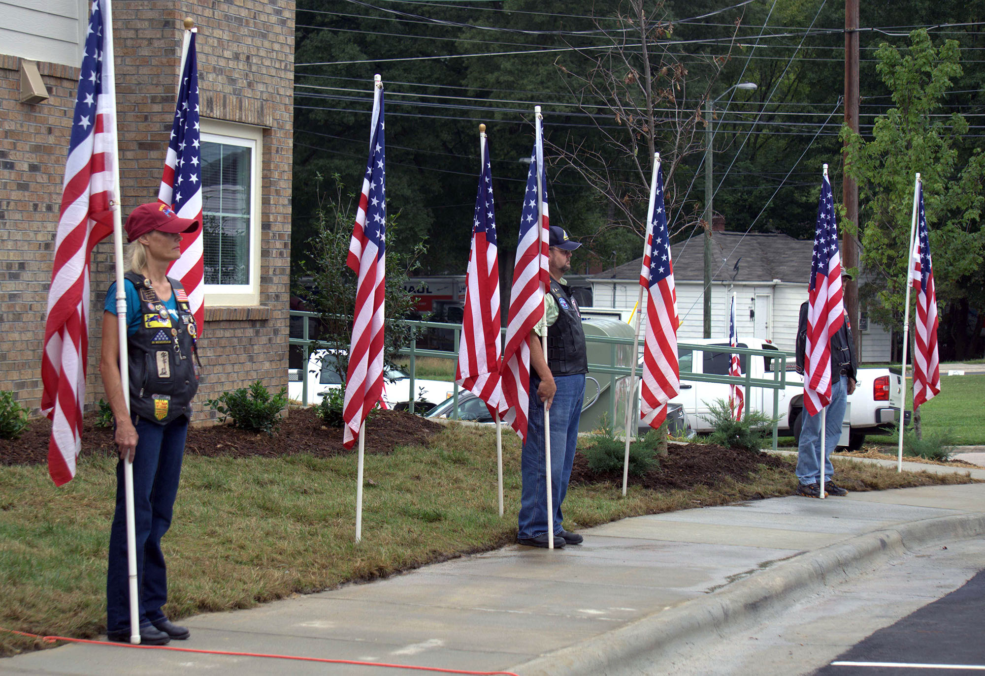 Veterans stand with American flags to celebrate the opening of the Denson Apartments in September. (Staff photo by Olivia Browning)