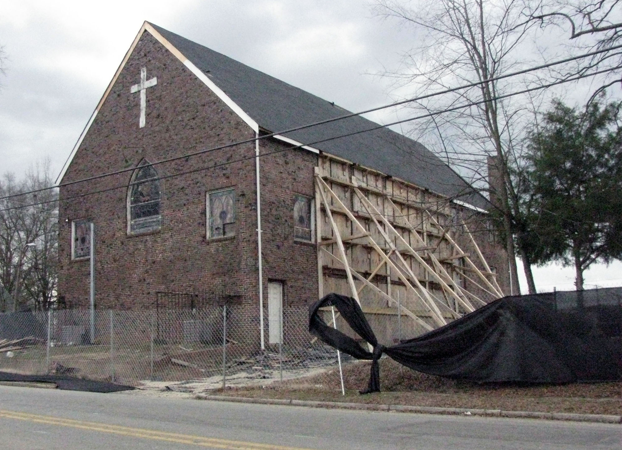 The church has focused primarily on imminent structural concerns regarding the building. Currently, wooden beams support one external wall, and the building's doors are boarded up. (Staff photo by Catherine O'Neill)