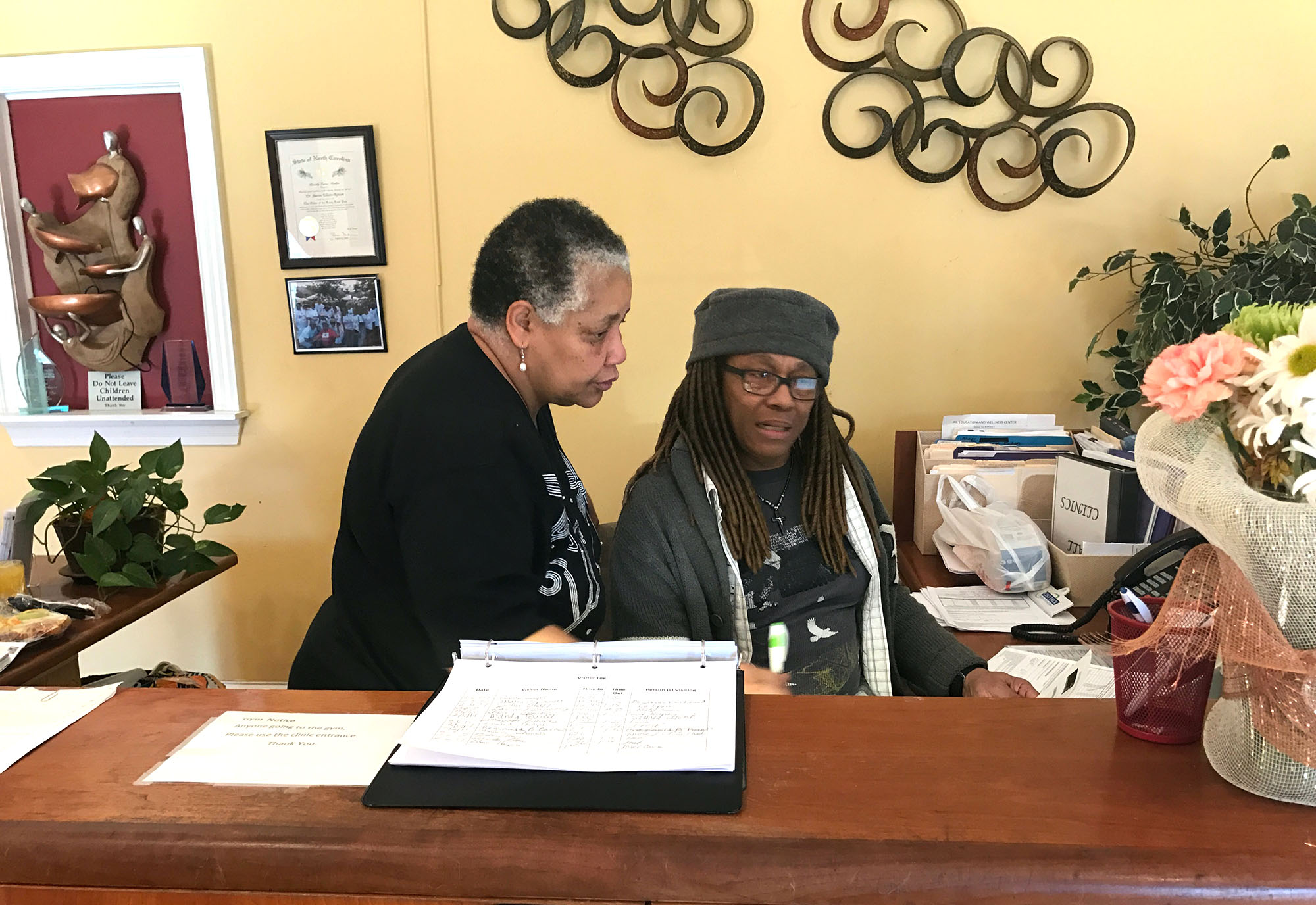 Renada Page and Carolyn Robinson review some work at the reception desk welcoming visitors. (Staff Photo by Ti-Vianna Webster)